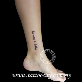 Tatuaje De La Frase La Vita E Bella En El Tobillo De Una Mujer