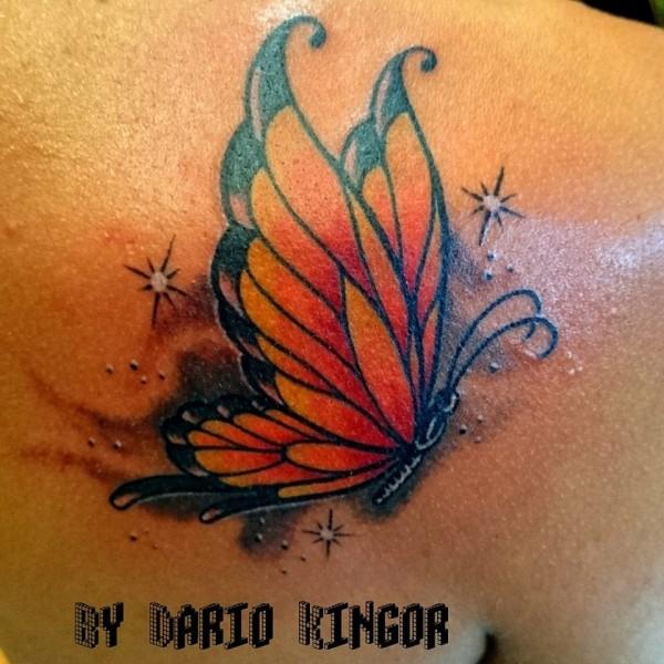 Tattoo de una mariposa a color volando bajo las estrellas