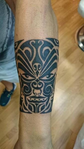 Tattoo De Una Mascara Maorí Formando Un Brazalete