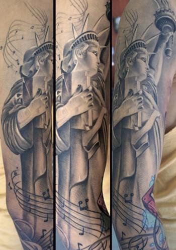 Tatuaje En El Brazo De La Estatua De La Libertad Con La Llama De