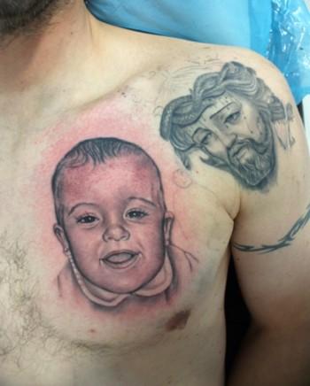 Tatuaje De Un Bebe En El Pecho Y Un Cristo En El Hombro
