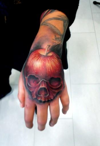 Tatuaje A Color En La Mano De Una Calavera Con Forma De Manzana