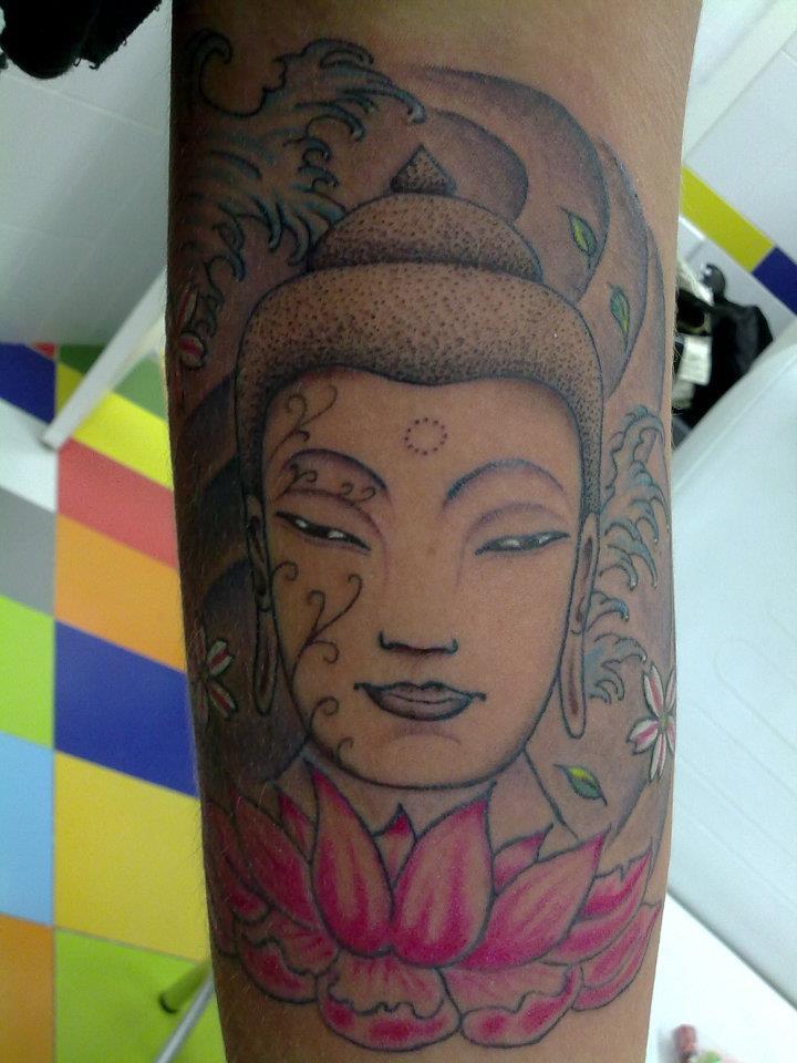 Tatuaje De Una Cabeza De Buda Entre Olas Y Encima De Una Flor De Loto