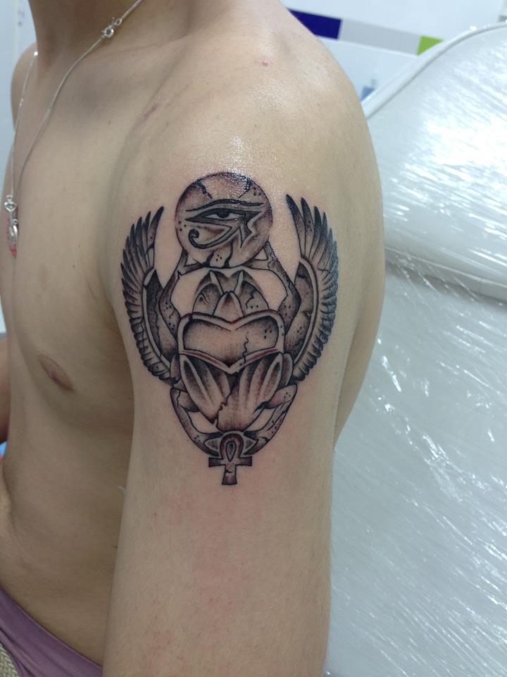 Tatuaje De Un Escarabeo Sosteniendo Un Ojo De Horus Y Una Cruz Ansada