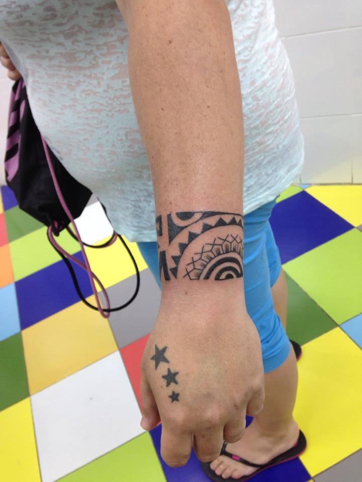 Tatuaje De Un Brazalete Maorí En El Brazo Y Algunas Estrellas En La