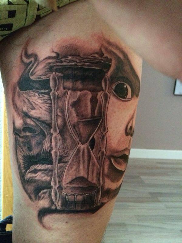 Tatuaje De Dos Caras Fantasmales Mirando Un Reloj De Arena