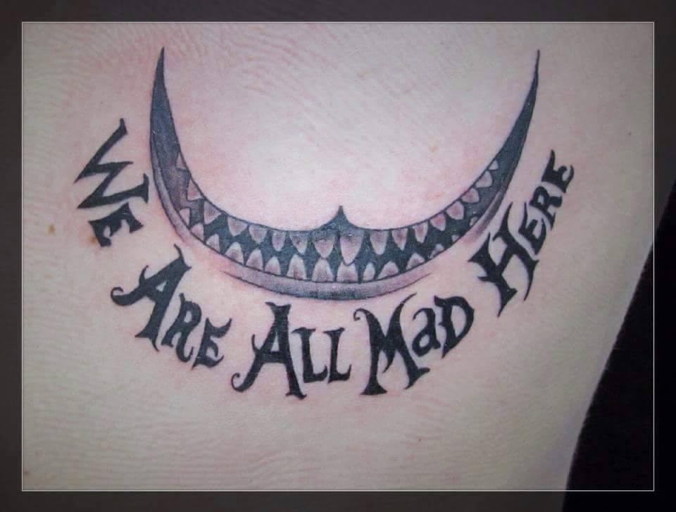 Tattoo De La Sonrisa Del Gato De Cheshire Con Una Frase Debajo