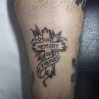 Tatuaje de una cruz y la frase In memory of my enemies
